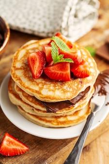 Gustosi appetitosi pancake appena sfornati decorati con pasta di fragole e cioccolato serviti a colazione. avvicinamento