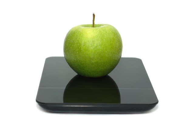 Gustosa mela verde appetitosa sulla bilancia da cucina isolata