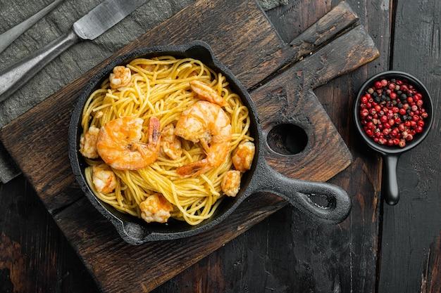 Gustosi e appetitosi spaghetti di pasta con salsa al pesto e set di gamberi, in padella in ghisa, su un vecchio tavolo di legno scuro, vista dall'alto piatta