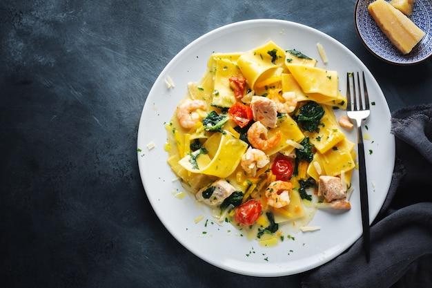 Gustosa pasta appetitosa con gamberi, verdure e spinaci servita sul piatto. vista dall'alto