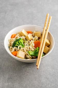 La minestra asiatica vegana appetitosa saporita con il tofu, le tagliatelle e le verdure è servito in ciotola sulla tavola concreta. avvicinamento.