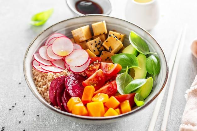 La ciotola vegan appetitosa saporita con le verdure e il tofu è servita in ciotola. avvicinamento.