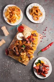 Gustosi snack alla birra assortiti: patatine, salsicce, anelli di cipolla, bocconcini di pollo, crostini di pane, costolette affumicate, ali di pollo, salsa di pomodoro e aglio