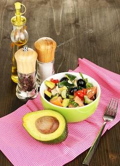 Insalata saporita dell'avocado in ciotola circondata dalle spezie sul primo piano del tavolo di legno