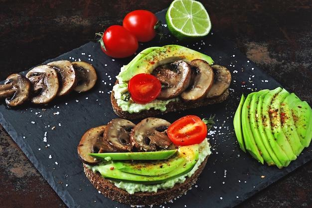 Gustosi toast con avocado con funghi e pomodorini, serviti su una tavola di pietra.