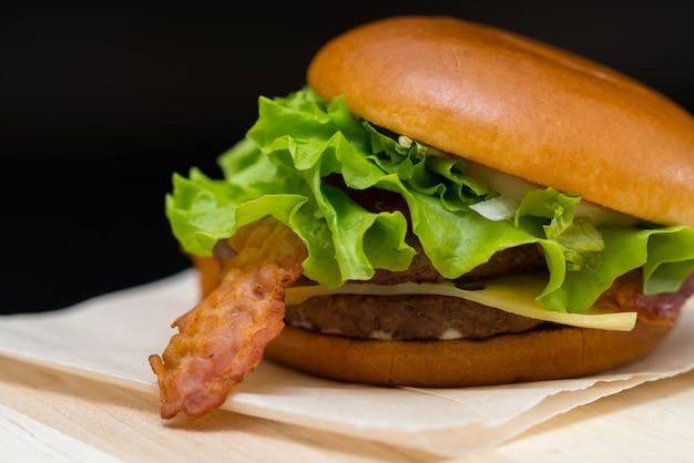 Gustoso bacon e cheeseburger con guarnizione di lattuga su un tovagliolo di carta servito come cibo da asporto o fast food in una caffetteria
