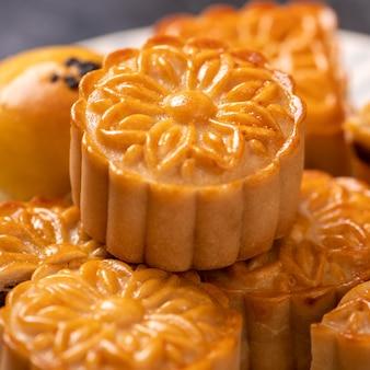 Gustosa torta al forno con pasta di tuorlo d'uovo per il mid-autumn festival su sfondo scuro di ardesia nera. concetto di cibo festivo cinese, primo piano, copia dello spazio. Foto Premium