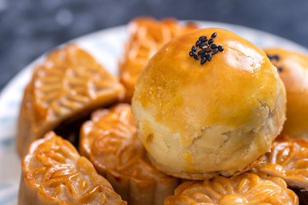 Gustosa torta al forno con pasta di tuorlo d'uovo per il mid-autumn festival su sfondo scuro di ardesia nera. concetto di cibo festivo cinese, primo piano, copia dello spazio.