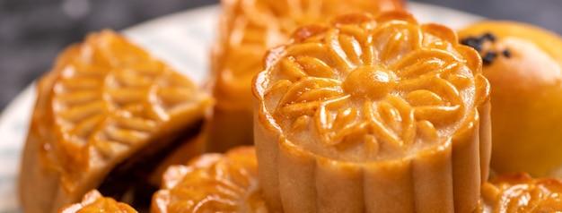 Torta di luna gustosa pasta al tuorlo d'uovo al forno per mid-autumn festival su sfondo luminoso tavolo di cemento. concetto di cibo tradizionale cinese, close up, copia dello spazio.