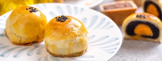 Gustosa torta al forno con pasta di tuorlo d'uovo per il mid-autumn festival su sfondo luminoso tavolo di cemento concetto di cibo tradizionale cinese, primo piano, copia dello spazio.