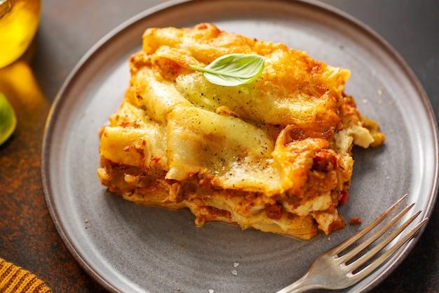 Gustose lasagne italiane preparate al forno classiche in casseruola su sfondo luminoso. avvicinamento