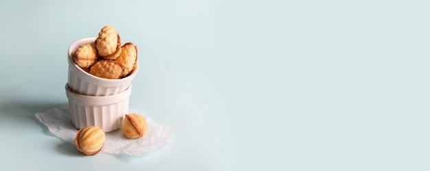 Gustosa composizione di cibo banner con biscotti di noce forma coni su sfondo blu con spazio di copia. concetto di spuntino sano cibo
