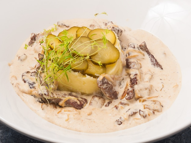 Gustoso manzo alla stroganoff con purè di patate su un piatto bianco