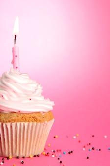 Gustoso cupcake compleanno con candela, sul rosa