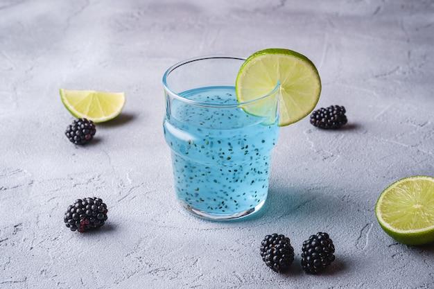 Gustosa bevanda cocktail di colore blu con semi di chia basilico, fetta di agrumi lime e mora in vetro, bevanda estiva sana, sfondo di pietra di cemento, vista di angolo