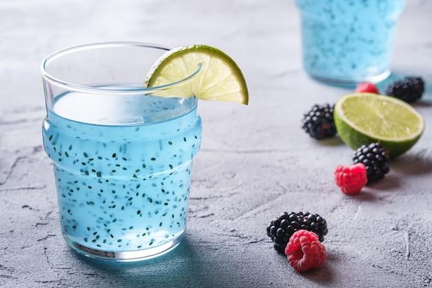 Gustoso cocktail di colore blu con semi di chia basilico, fetta di limone e agrumi, lamponi e bacche di mora in vetro
