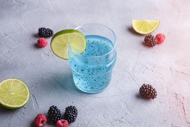 Gustoso cocktail di colore blu con semi di basilico chia, fetta di limone e agrumi, lamponi e bacche di mora in vetro