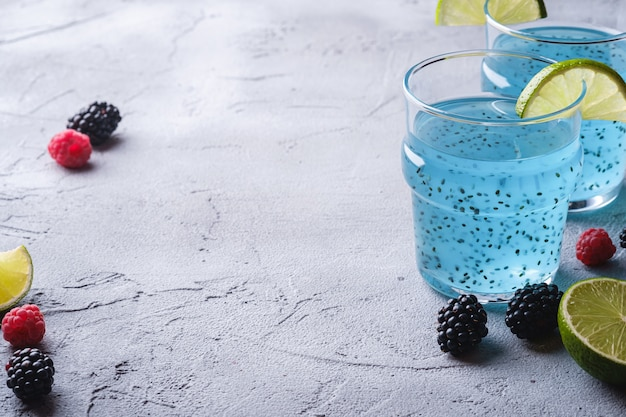 Gustoso cocktail di colore blu con semi di chia basilico, fetta di limone e agrumi, lampone e bacche di mora in due bicchieri
