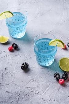 Gustoso cocktail di colore blu con semi di chia basilico, fetta di limone e limone, lamponi e bacche di mora