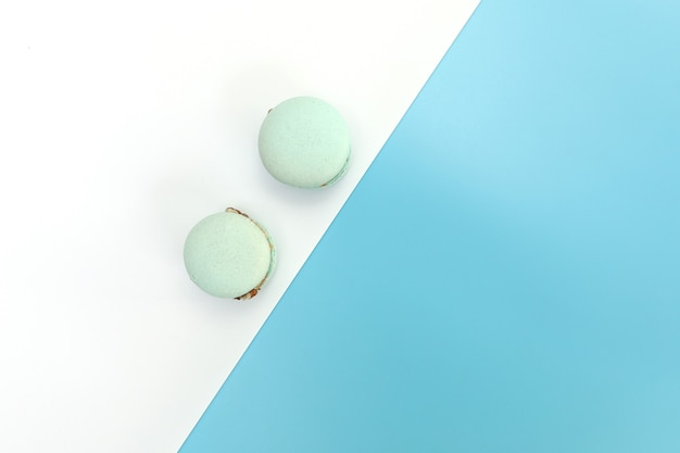Gustosi macarons francesi blu o amaretti su uno sfondo bianco e blu.
