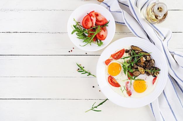 Gustosa colazione: uova fritte, funghi di bosco, pomodori e rucola. cibo per il pranzo. vista dall'alto, sovraccarico, copia dello spazio