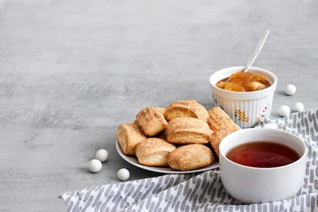Gustosa colazione. biscotti dolci fatti in casa alla cannella e tazza di tè. confettura di mele sullo sfondo. copia spazio