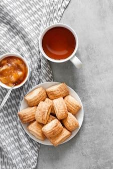 Gustosa colazione. biscotti dolci fatti in casa alla cannella, tazza di tè e confettura di mele. appartamento laico, vista dall'alto, copia dello spazio