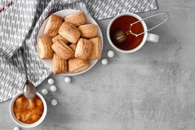 Gustosa colazione. biscotti dolci fatti in casa alla cannella, tazza di tè e confettura di mele. flatlay, vista dall'alto, copia dello spazio