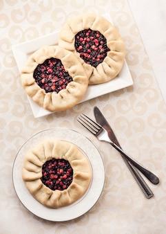 Gustosa colazione. galette dolce fatto in casa con bacche di sambuco e mirtilli rossi su un piatto. vista piana laico e dall'alto