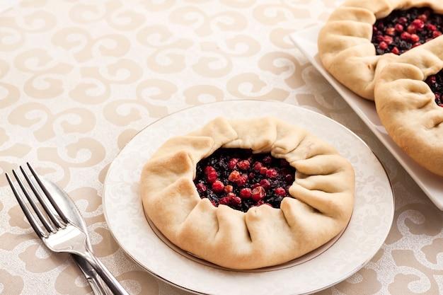 Gustosa colazione. galette dolce fatto in casa con bacche di sambuco e mirtilli rossi su un piatto con copia spazio
