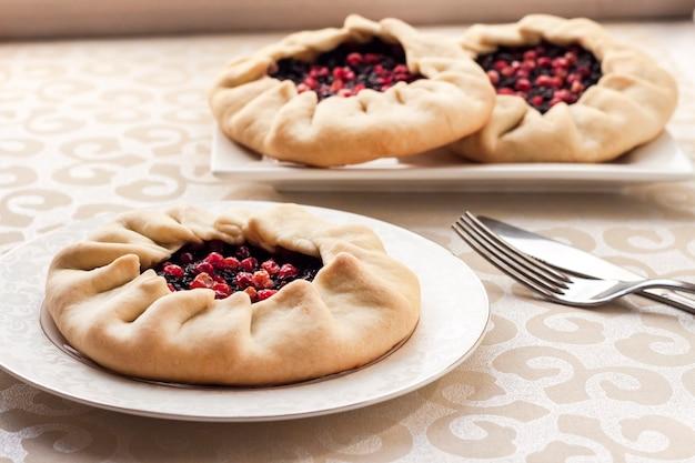 Gustosa colazione galette dolce fatta in casa con bacche di sambuco e mirtilli rossi su un piatto