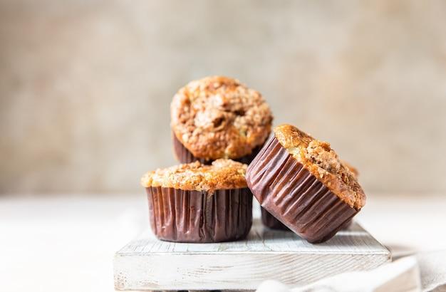 Gustosi muffin per la colazione con briciole di avena guarnita su un tagliere bianco superficie di cemento