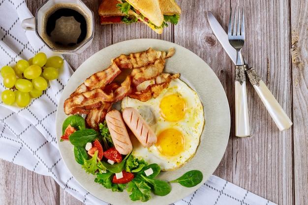 Gustosa colazione con uova, salsicce, pancetta e tazza di caffè.
