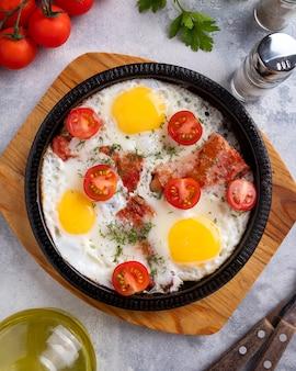Gustosa colazione con uova fritte, pancetta e verdure su una padella. vista dall'alto. avvicinamento