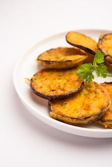 Gustoso brinjal pakora o frittelle di melanzane croccanti, snack indiano per l'ora del tè servito con chutney verde