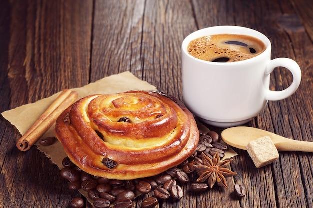 Panino gustoso con uvetta e tazza di caffè caldo su un tavolo di legno vintage
