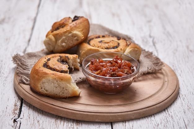 Gustosi panini con uvetta su un tavolo di legno rustico bianco. panetteria fresca. colazione. pane. vista dall'alto