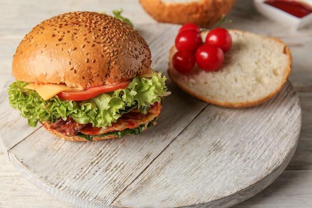 Gustosi hamburger, panino e pomodoro su tavola di legno
