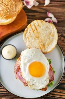 Gustoso hamburger con pancetta e uovo fritto sul tavolo