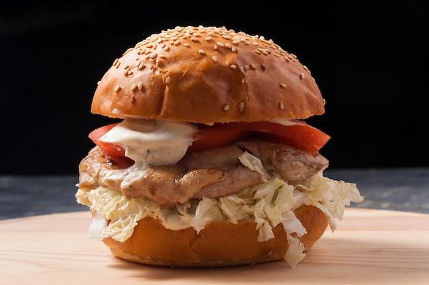 Gustoso hamburger con filetto di pollo, pomodori, lattuga su sfondo nero
