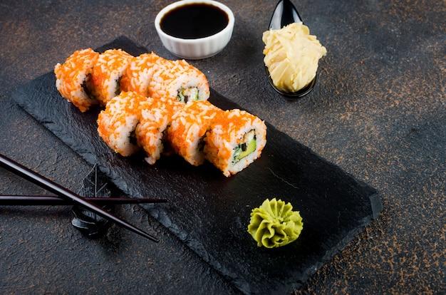 Gustosi panini california e maki su lastra di pietra con salse, bacchette, zenzero e wasabi