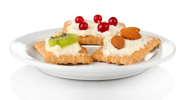 Gustosi tartine con formaggio, kiwi e mirtillo rosso, mandorle, su tavola di colore, su bianco