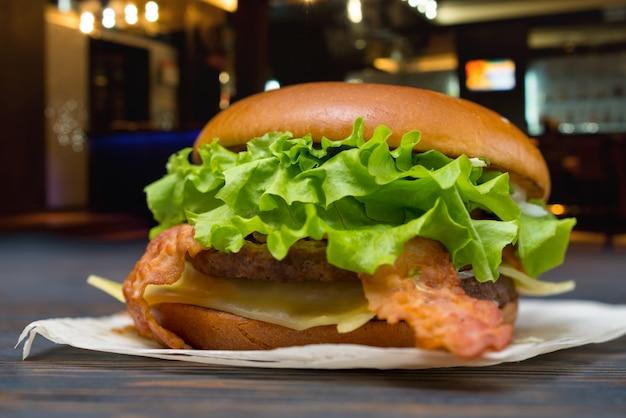 Gustoso hamburger di formaggio e pancetta con guarnizione di lattuga fresca in una vista a basso angolo su un tovagliolo di carta all'aperto su un tavolo nella strada della città di notte