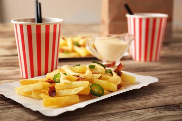 Gustose patatine al formaggio e tazze di acqua gassata su un tavolo di legno
