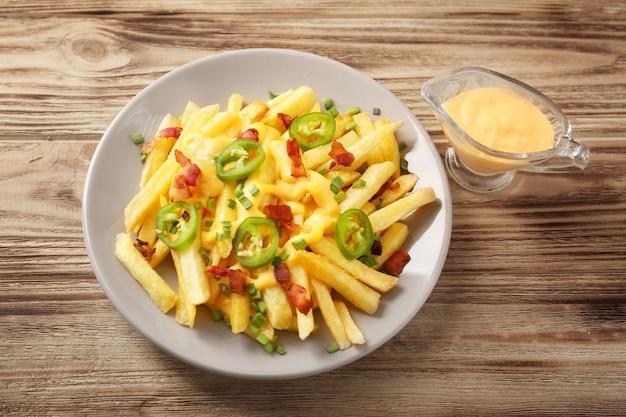 Gustose patatine al formaggio con pepe e salsa a fette su un tavolo di legno