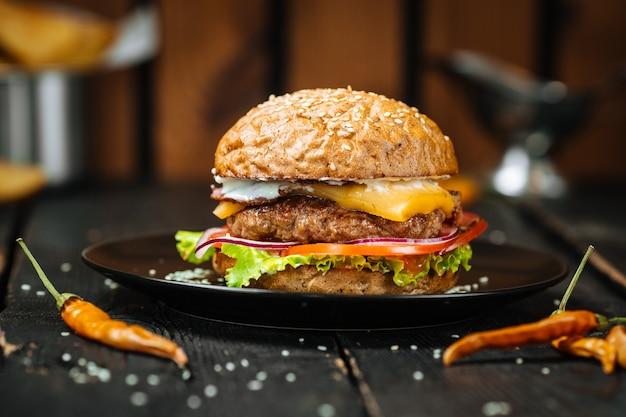 Cheeseburger saporito su una tavola di legno scura