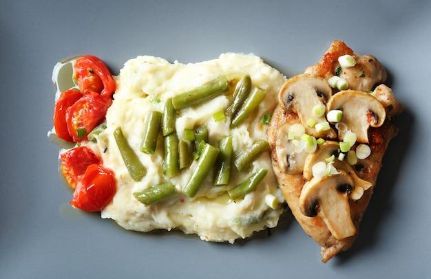 Marsala saporito del pollo con le verdure sul piatto, primo piano
