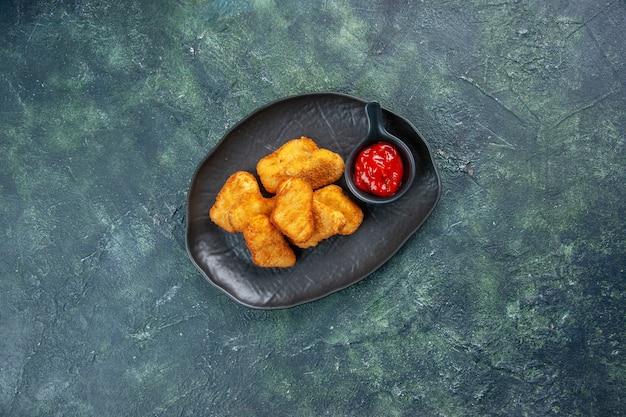 Gustosi bocconcini di pollo e ketchup in piatti neri su superficie scura