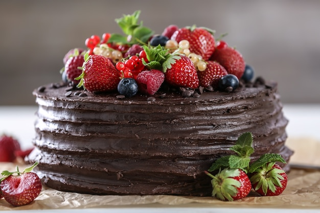 Gustosa torta al cioccolato decorata con frutti di bosco sul tavolo
