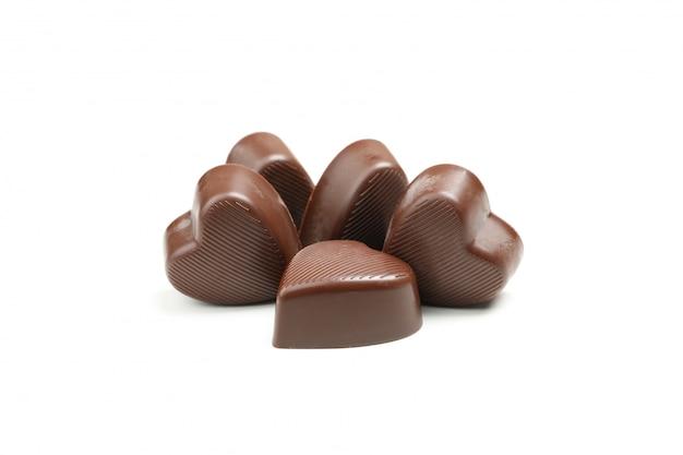 Caramelle di cioccolato saporite sotto forma di cuore isolate su bianco